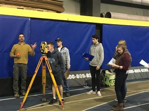 Students learning to use surveying equipment
